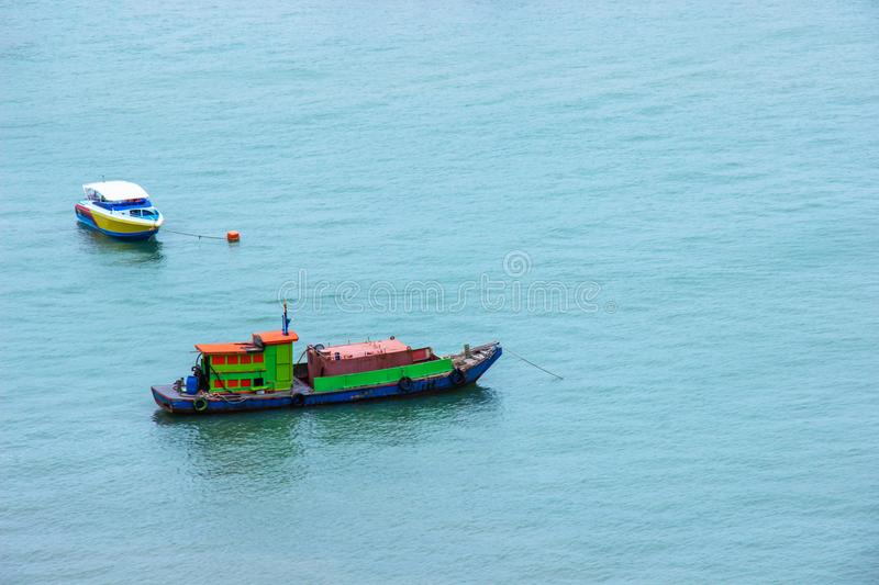 Traditional fishing boat and speed boat floating in the sea after send the tourists. stock photos