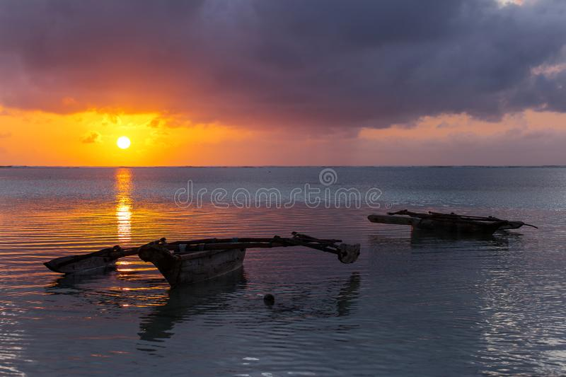 Traditional fishing boat in Zanzibar with storm clouds at sunrise stock photography