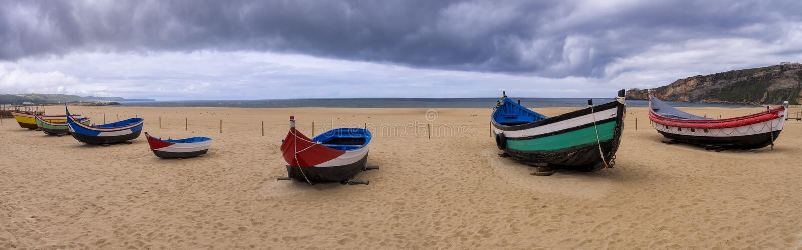 Traditional fishing boats, Nazare, Portugal. A panorama of several traditional colourful fishing boats on Nazare beach, Portugal stock photo