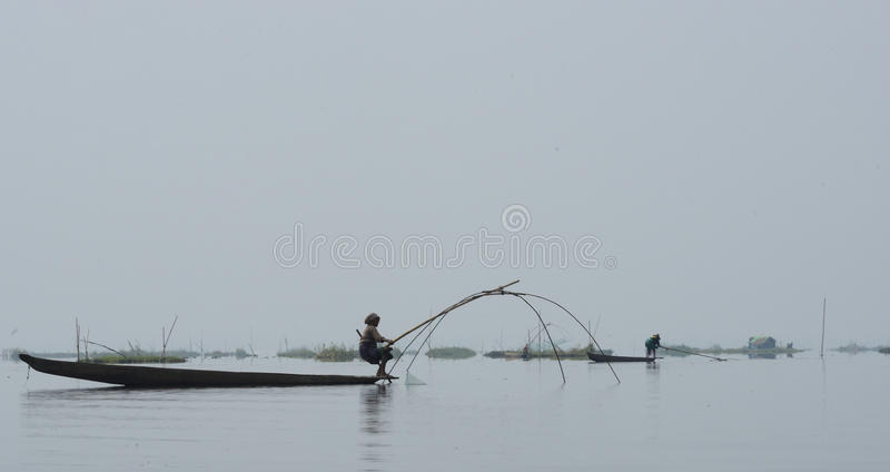 Woman on canoe Fishing in lake stock image