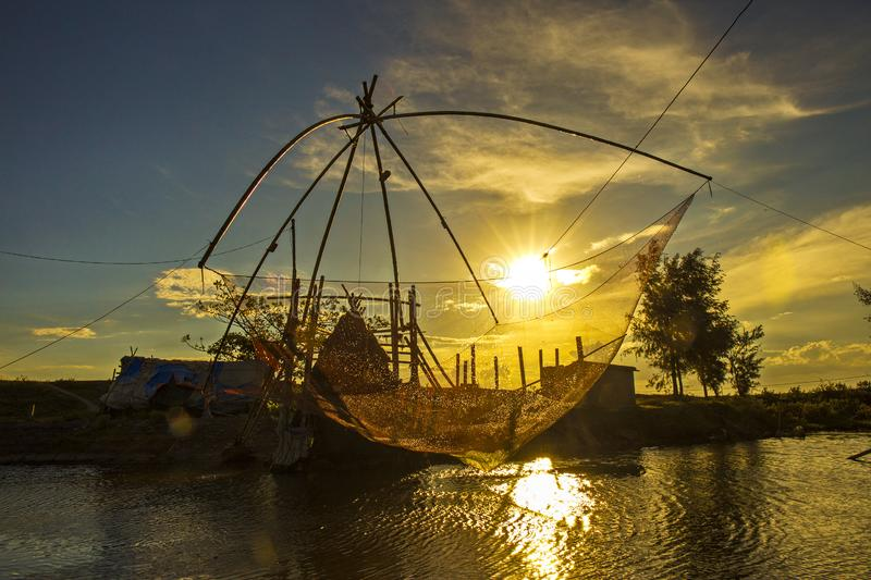 A traditional fishing net with bamboo frames on the river at sunset. royalty free stock photo