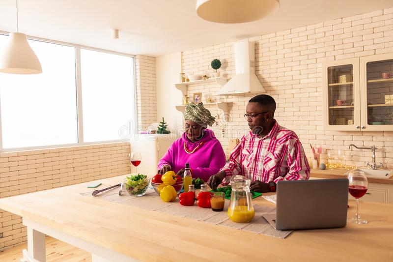 Pleasant nice African couple cooking lunch together. Traditional food. Pleasant African couple cutting vegetable while cooking lunch together royalty free stock photography