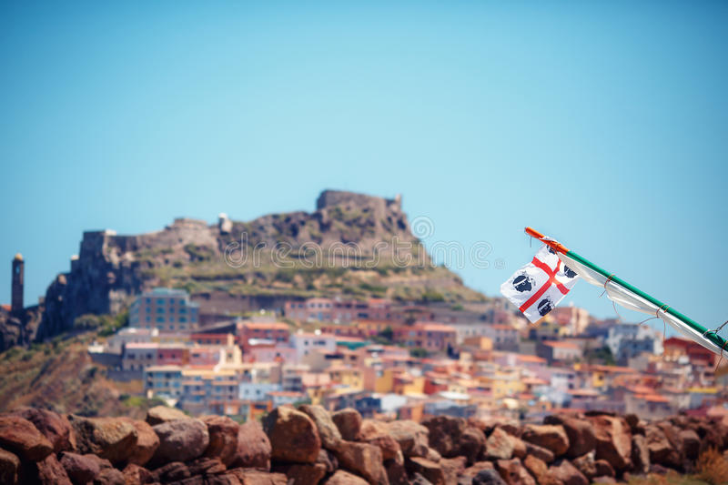 Traditional Four Moors flag of Sardinia`s Region against Medieval town Castelsardo. Sardinia, Italy royalty free stock image