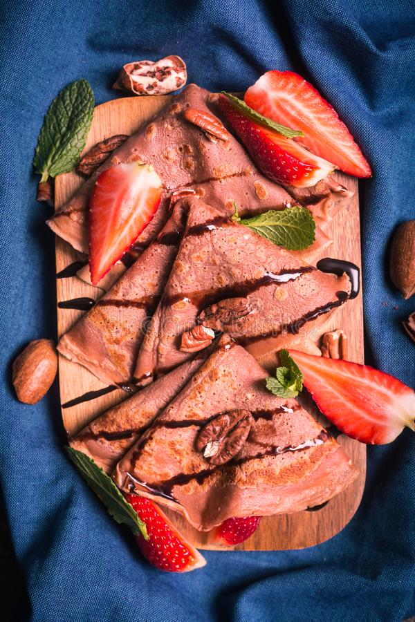 Traditional French crepes cooked with chocolate. Decorated with mint and strawberries stock photos