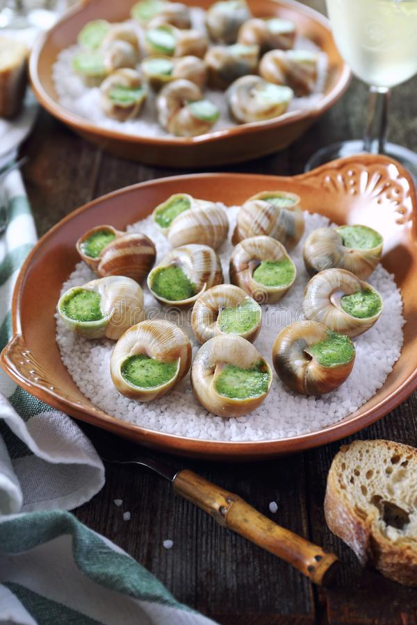 Traditional French dish: snails with sauce Burgundy and glass of wine. Escargots, traditional French cuisine: snails with sauce Burgundy and a glass of white royalty free stock photos