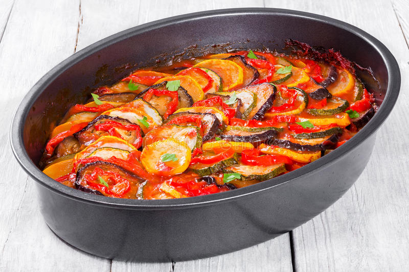 Traditional French vegetable casserole ratatouille, top view. Traditional French casserole - ratatouille: stewed zucchini, red bell pepper, parsley, yellow royalty free stock photos
