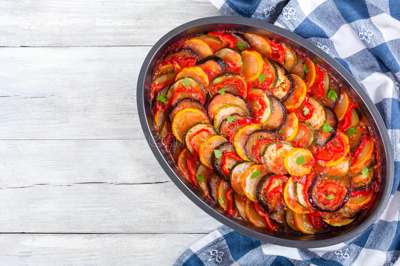 Traditional French vegetable casserole ratatouille, top view. Traditional French casserole - ratatouille: stewed zucchini, red bell pepper, parsley, yellow royalty free stock images