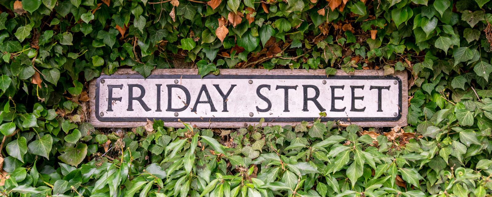 Traditional Friday Street road sign, England, United Kingdom. Friday Street road sign surrounded by leaves, England, United Kingdom stock images