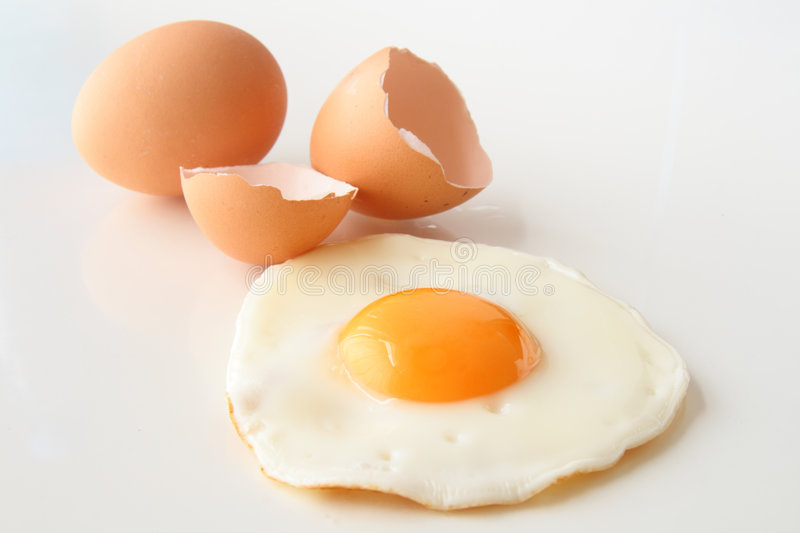 Traditional fried egg with cracked shell and whole egg stock images