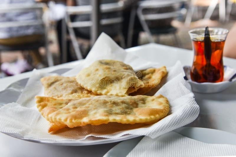 Traditional fried pastry called `çi börek` made with raw ground meat, onions, and spices served  with Turkish tea, close up stock photo