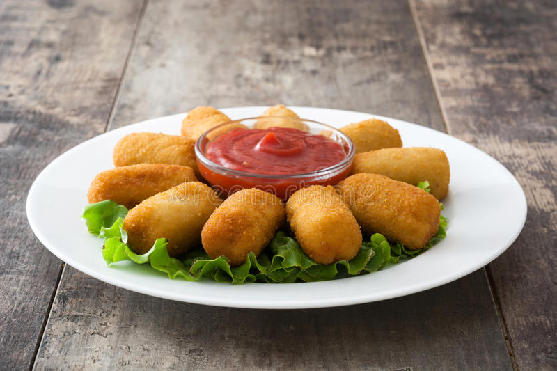 Traditional fried Spanish croquetas croquettes with ketchup in plate. On wooden background.copyspace royalty free stock images