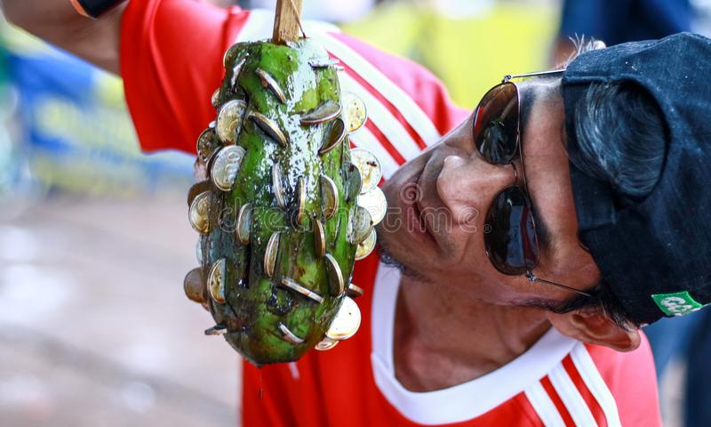 Traditional game in Indonesia. Depok, Indonesia - August 17, 2019: People take coins from oiled fruit. Traditional game to commemorate Indonesia`s independence royalty free stock image