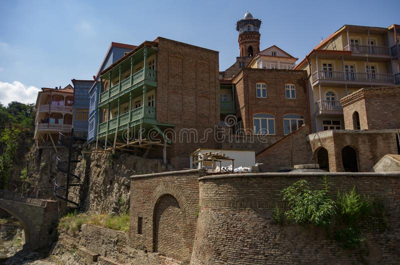 Traditional georgian architecture with  wooden balconies in Abanotubani historical part of Tbilisi. Near waterfall in botanical garden.Georgia, unesco heritage stock photography