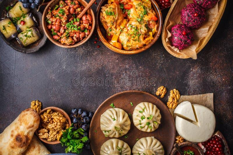Traditional Georgian cuisine background. Khinkali, phali, chahokhbili, lobio, cheese, eggplant rolls, dark background. Traditional Georgian cuisine background stock images