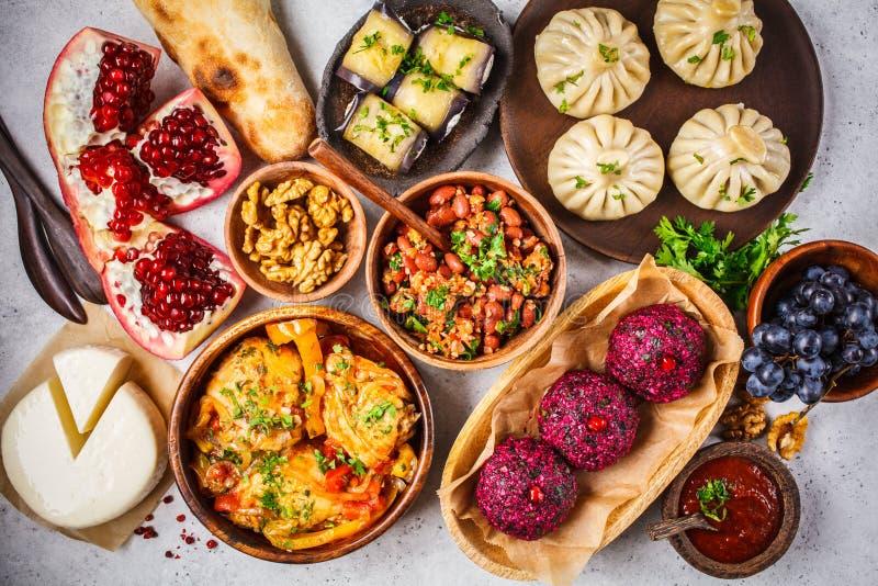 Traditional Georgian cuisine background. Khinkali, phali, chahokhbili, lobio, cheese, eggplant rolls on white background. Top view royalty free stock photos