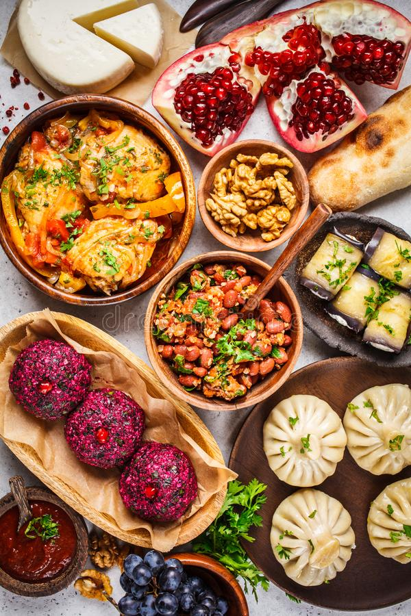 Traditional Georgian cuisine background. Khinkali, phali, chahokhbili, lobio, cheese, eggplant rolls on white background. Top view stock images