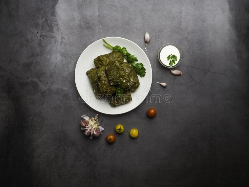 Traditional georgian dolma in grape leaves on rustic wooden table with copyspace stock image