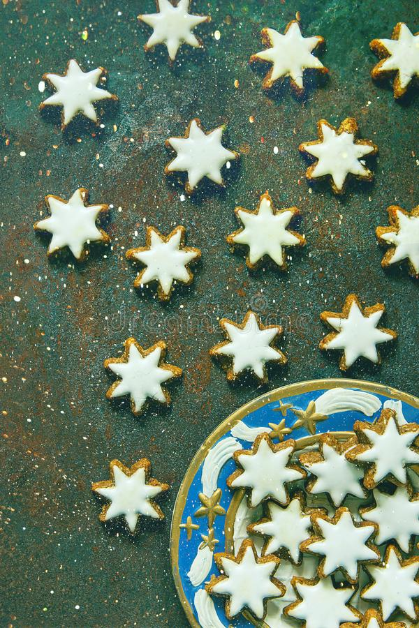 Traditional German Christmas Cookies Home Baked Glazed Cinnamon Stars with Nuts on Blue Plate Rusty Dark Green Background. Glitter royalty free stock photos