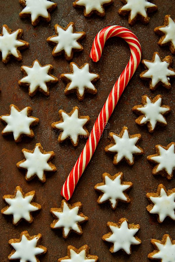 Traditional German Christmas Cookies Home Baked Glazed Cinnamon Stars with Nuts Candy Cane Pattern on Rusty Dark Background. Festive Magic Atmosphere royalty free stock images