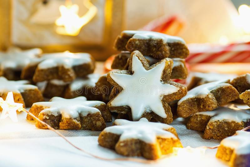 Traditional German Christmas Cookies Home Baked Glazed Cinnamon Stars with Nuts Sparkling Garland Lights Candle Candy Canes. On White Linen Background. Festive royalty free stock photos