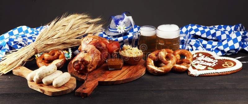 Traditional German cuisine, Schweinshaxe roasted ham hock. Beer, pretzels and various Bavarian specialties. Oktoberfest background royalty free stock images