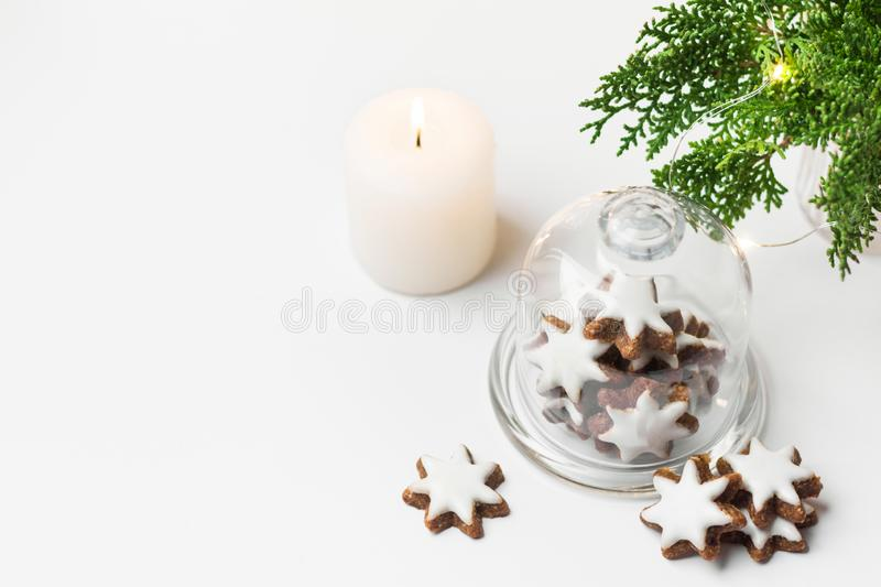 Traditional German star shaped cinnamon cookies with icing in cloche dome bell glass jar on white table. Lit candle juniper. With golden garland lights. Magic royalty free stock images