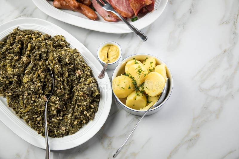 Traditional German winter dish Oldenburger green cabbage with sausage mix, Kassler pork neck on platter with boiled potatoes and royalty free stock photo