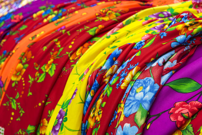Traditional gipsy dresses fabrics. Detail of colorful traditional gipsy dresses fabrics with floral patterns. Shallow depth of field stock photography