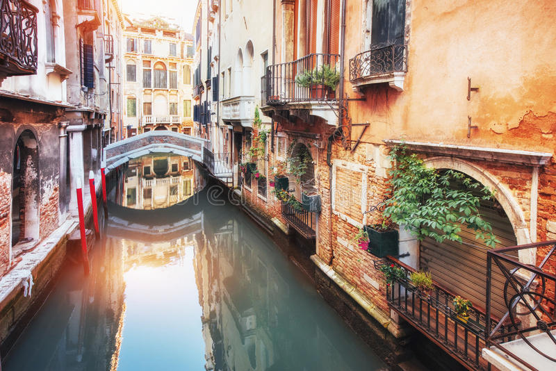 Traditional Gondolas on narrow canal between colorful historic houses in Venice Italy stock images