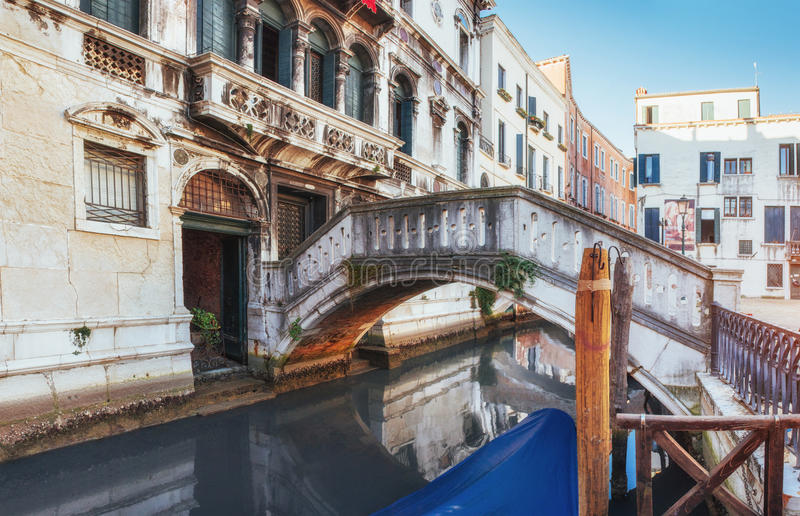 Traditional Gondolas on narrow canal between colorful historic houses in Venice Italy stock photos