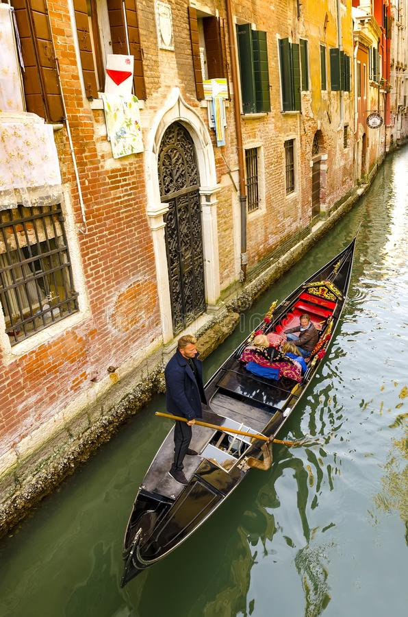 Traditional Gondolas on narrow canal between colorful historic houses in Venice stock photo