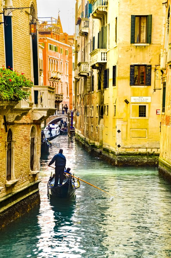 Traditional gondolas on narrow canal in Venice, Italy stock images