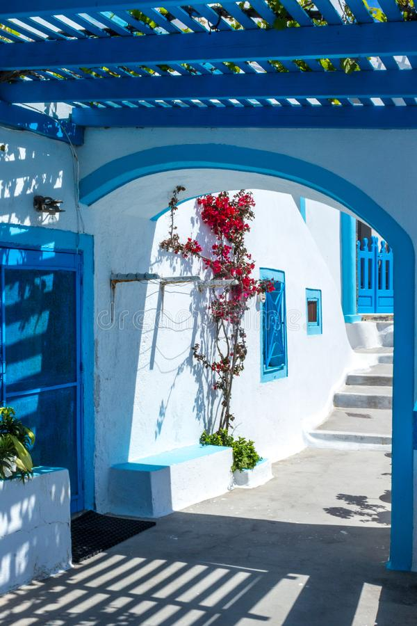 Traditional Greek architecture with whitewashed walls and blue pergola.ni. royalty free stock photography