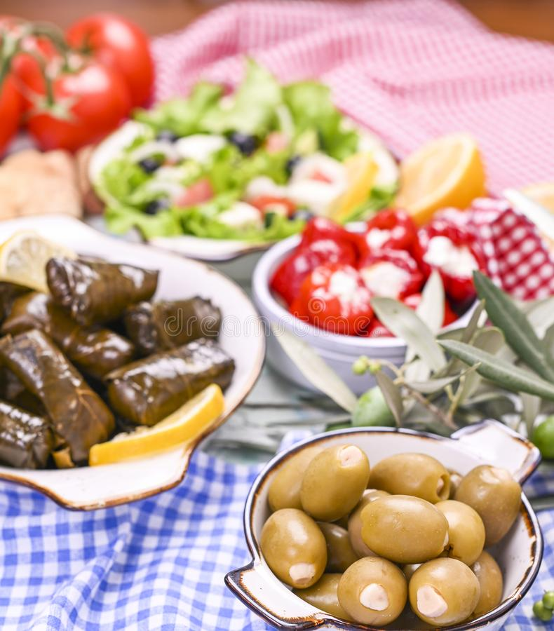 Traditional greek cuisine. Wrapped rice in grape leaves. Dolma with lemon, spices and greek salad. Home cooked food. Olive royalty free stock photos