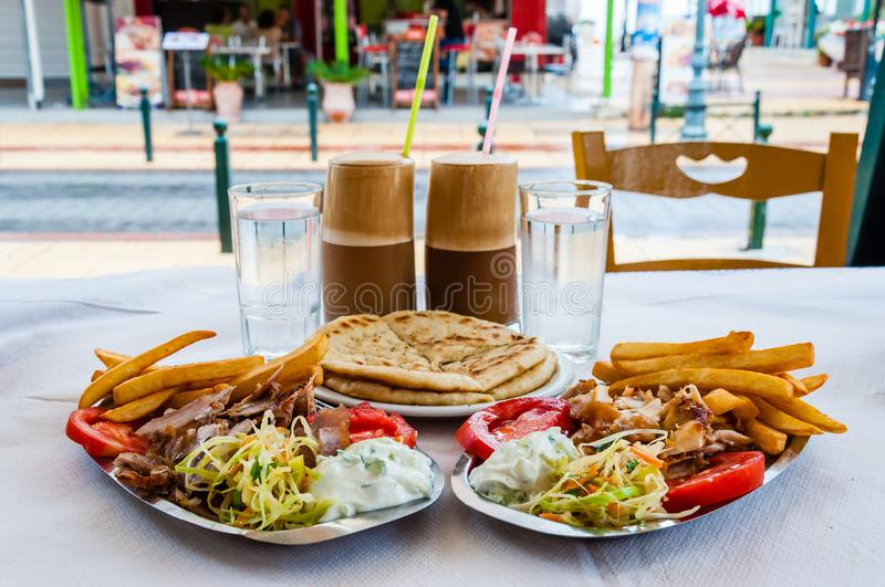 Traditional Greek hot dish Gyro or Gyros served on the plates. Pork or chicken meat, flat bread pita, tomato, tzatziki sauce, and stock photo