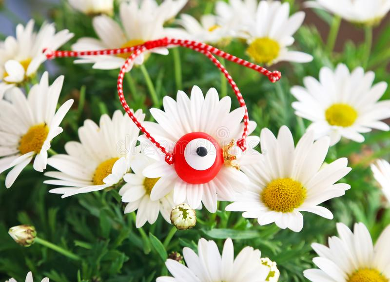 Traditional greek March bracelet with evil eye on blooming daisy flowers. Traditional protection jewelry stock image