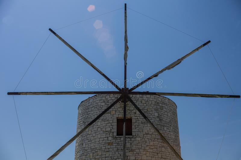 Traditional Greek Windmill with Eight Metal Blades. Medieval Landmark for Sightseeing. Brick Layered White Old Circular. Fortress Standing under Blue Sky royalty free stock photo