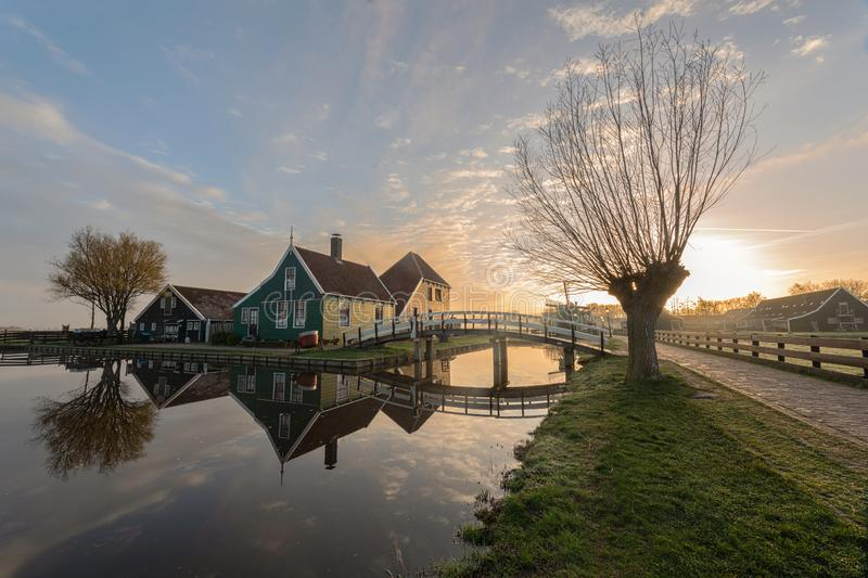 Traditional green dutch house with little wooden bridge against blue sky in the Zaanse Schans village stock photo
