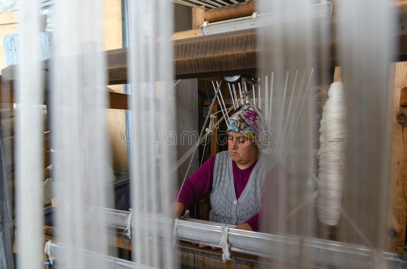 Traditional hand weaving in the Kastamonu in Turkey. Kastamonu,TURKEY-November 05,2017: Woman working at the loom. Turkey national crafts. Focused on the woman royalty free stock images