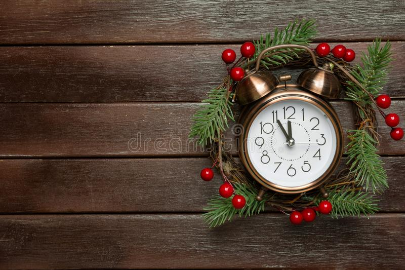 Traditional handmade Christmas wreath with green fir tree branches holly berries clock showing five minutes to midnight countdown royalty free stock images