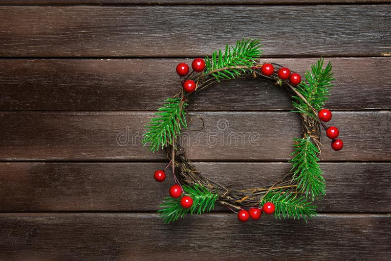 Traditional Handmade Christmas Wreath Green Fir Tree Branches Twigs Holly Berries on Dark Plank Wood Background. Top View. Flat Lay. Greeting Card Poster stock photos