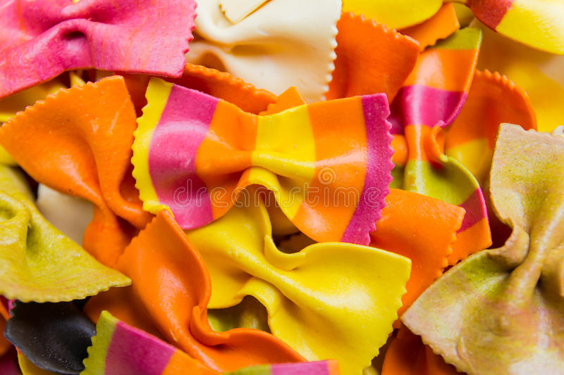 Traditional handmade italian farfalle pastas. Close up colored background royalty free stock image
