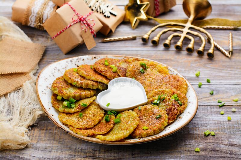 Traditional Hanukkah dish latkes. Potato pancakes with sour cream. Table decorated with menorah, gift boxes and candles stock images