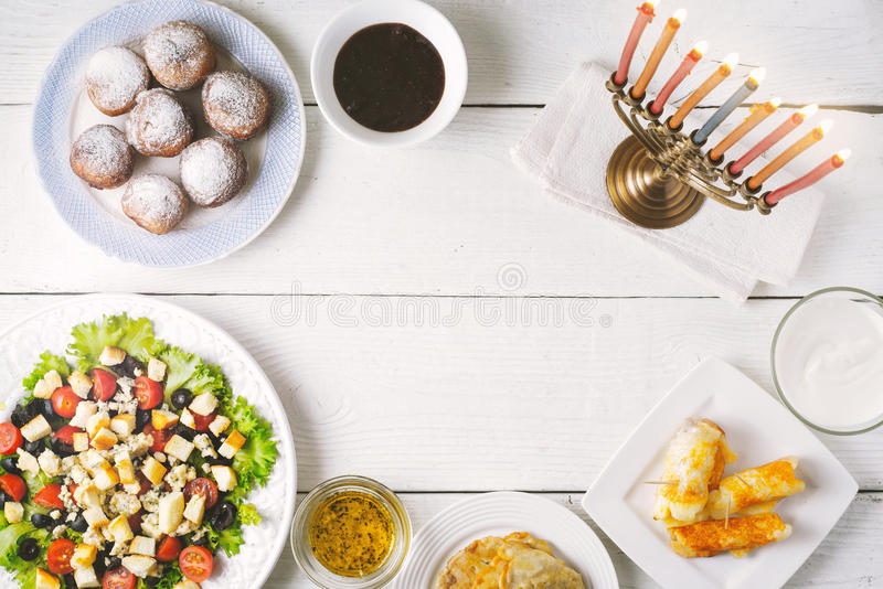 Traditional Hanukkah dishes on the white wooden table stock photo
