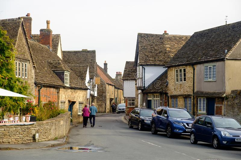 A senior couple walks in the streets of Lacock royalty free stock photography