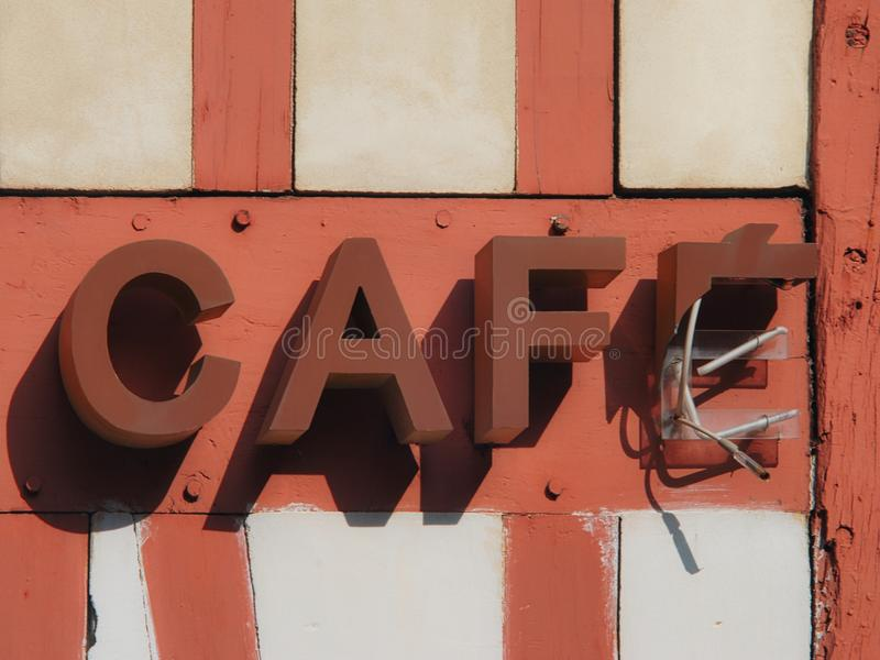 Broken `CAFÉ` neon sign in the street in France. A traditional historical house `maison en colombages` in France with a broken neon sign royalty free stock photo