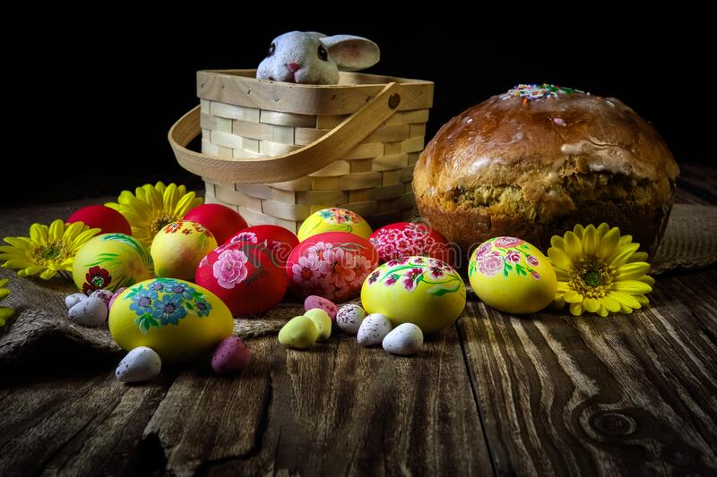 Traditional holiday composition. Hand painting Easter eggs with orthodox sweet bread on a dark wooden table. With rabbit figure. royalty free stock photo