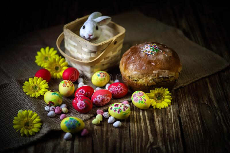 Traditional holiday composition. Hand painting Easter eggs with orthodox sweet bread on a dark wooden table. With rabbit figure. stock photos