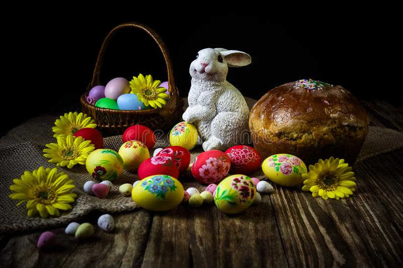 Traditional holiday composition. Hand painting Easter eggs with orthodox sweet bread on a dark wooden table. With rabbit figure. stock photography