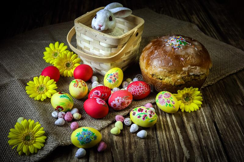 Traditional holiday composition. Hand painting Easter eggs with orthodox sweet bread on a dark wooden table. With rabbit figure. stock images